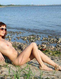 Beautiful and limber Renata enjoys relaxing moments nude on the beach
